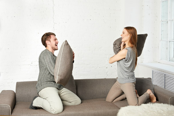 Happy Couple Fighting with Pillows on Coach